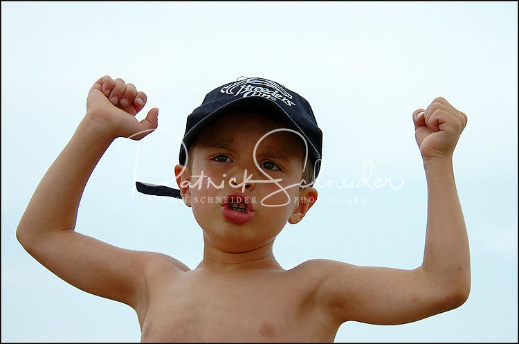 A young boy (model released) shows his muscles - and enthusiasm - at the beach. Photo taken on Sullivan's Island, near Charleston, South Carolina beach on the Atlantic Ocean, but could represent a beach scene anywhere.