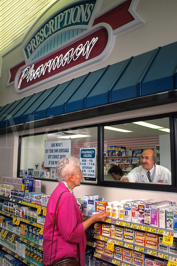Old lady talks with pharmacist at Pharmacy about medicine prescription and discussing health.