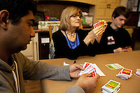 USA. Washington state. Fall City. ReStart Internet Addiction Recovery program at Heavensfield Retreat Center. Shlok (L), Rosanne Sherlock (R) and Andrew(R) seat and play cards (apples to apples' game) on the living room's table. Rosanne Sherlock is the daytime resident superviser. Shlok is 22 years old and is a citizen from India. Andrew is 20 and american. Both have dropped out of university because they were highly addictive online video gamers on internet. ReStart is an unique intensive onsite program which offers to participants an opportunity to stay in a retreat center designed to promote insight and renewal, disconnect from digital distractions, and engage in coaching and mentoring while building a blue print for change. The three to six-month reStart program, the first of this kind in the United States, works to help men over 18, suffering from problematic internet, video game, social media and technology use by teaching positive and sustainable lifestyle change in a serene, rural environment surrounded by nature. 11.12.2014 © 2014 Didier Ruef