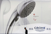 A man Walks under an advertisement for German made bathroom wares at the International Building and Construction Trade Fair in Shanghai, China. China's continued building boom has made it the largest market in the world for building materials from end product like shower heads to raw material such as timber..