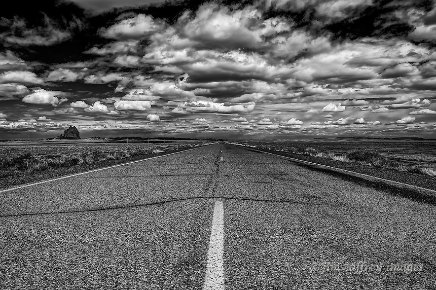A black and white image of Indian Route 13 under a stormy sky as it approaches Shiprock in northwestern New Mexico.