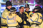 """© Joel Goodman - 07973 332324 . NO SYNDICATION PERMITTED . CAUTION RE ID OF MAN RECEIVING TREATMENT . 20/12/2014 . Manchester , UK . Police tend to a vomiting man with a head injury outside Deansgate Locks nightclub venue . An ambulance took over 40 minutes to arrive . """" Mad Friday """" revellers out in the rain and cold in Manchester . Mad Friday is typically the busiest day of the year for emergency services , taking place on the last Friday before Christmas when office Christmas parties and Christmas revellers enjoy a night out .  Photo credit : Joel Goodman"""