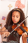8 year old girl at home musical instrument practice portrait playing violin vertical