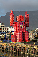 """South Africa, Cape Town. """"Lego Man"""" sculpture made of 4200 plastic  Coca Cola crates.  Designed by Porky Hefer.  Victoria & Alfred Waterfront.  Table Mountain in background."""