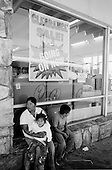 Nogales, Arizona.USA.October 20, 2006..Just off the port of entry to the USA a family waits near a store selling inexpensive items. The city is divided between Nogales Mexico and Nogales USA. The fence extends for several miles in either direction off the port of entry - then there is little to stop people from crossing illegally after the fence. Nogales is inhabited with mainly Mexicans, legal and illegal, and it is mostly a transit and shopping town.