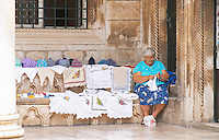 The arched porch of the Rector's Palace Knezev Dvor. An old woman selling embroideries, hats, table cloths and other decoration, to tourists while sitting embroidering or stitching on the Pred Dvorom street Dubrovnik, old city. Dalmatian Coast, Croatia, Europe.