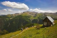 Hiker walks past a shepherd?s hut on the GR5 on Alpine pastures above the Roya Valley. Mont Mounier. Parc National du Mercantour. Alpes-Maritimes. Provence, France.   Model released.