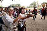 A girl holds up a bowl of cake toward the Queen's procession at the Renaissance Pleasure Faire at Santa Fe Dam Recreation Area, Los Angeles, County, CA