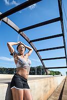 Healthy natural looking young African American female runner resting from marathon training on the 360 Bridge on Lake Austin, Texas.