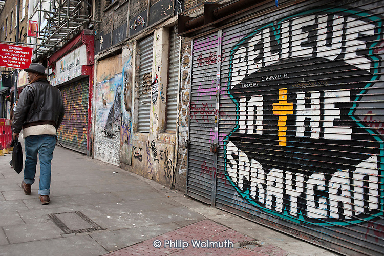 Believe in the Spraycan.  Graffiti and murals on empty shops on Bethnal Green Road, London.
