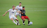 WASHINGTON, DC - AUGUST 25: Edison Flores #10 of D.C. United battles for the ball with Henry Kessler #4 and Matt Polster #8 of New England Revolution during a game between New England Revolution and D.C. United at Audi Field on August 25, 2020 in Washington, DC.
