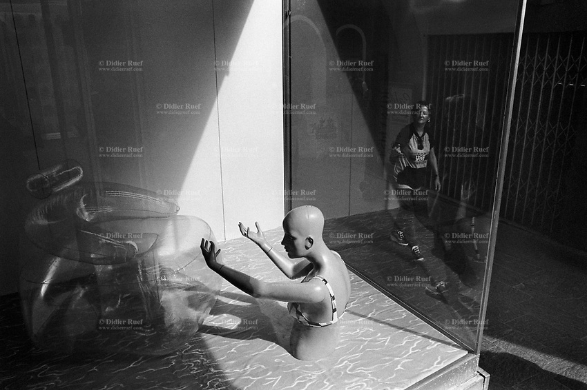 Italy. South Tyrol. Meran. A woman manikin with swimmsuit in a shop window. A plastic inflatable couch and a fake poool with water. Meran (in italian Merano) is a town and comune in South Tyrol. South Tyrol (German: Südtirol; Italian: Sudtirolo, also known by its alternative Italian name Alto Adige) is an autonomous province in northern Italy. 11.08.1999 © 1999 Didier Ruef