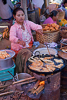 Myanmar, Burma.  Woman Cooking Bananas in Local Market, Inle Lake, Shan State.  She is wearing thanaka paste on her face, a Burmese cosmetic sunscreen.