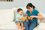 21 month old toddler boy at home playing game with mother making animal figures toy tigers talk and play with each other