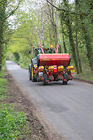 Tractor and drill moving on the road to another field - May; Norfolk