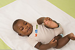 5 month old baby boy African American lying on back grasping foot horizontal
