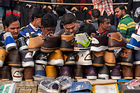 Men look at shoes on display for sale at the street market on Meena Bazar in the Chadni Chowk area of Delhi, India, on Tue., Dec. 11, 2018.