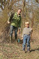 Kind, Junge und Vater tragen Weidenruten, Weidenzweige im Bündel, die von einer Kopfweide abgeschnitten wurden