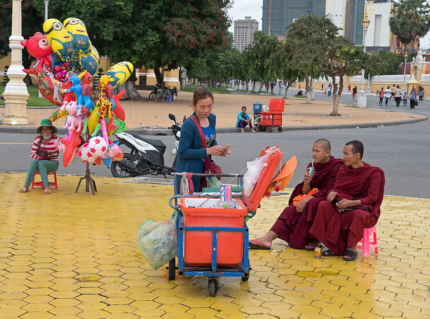 Phnom Penh street scenes and people during the Monsoon season and heavy rains. Cambodia Buddhist Monks having a soft drink after the rain,