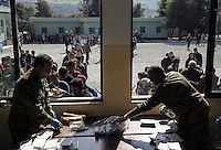 Pictured: Army officers hand over food to the hundreds of refugees Friday 26 February 2016<br /> Re: Hundreds of refugees have been given temporary shelter at the Stefanakis Army Camp in the Schisto area of Athens, Greece.