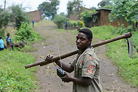 RUANDA, Ruhengeri, Virunga Mountains, farmer with hoe and chinese X-Bass  radio / Virunga Berg- und Vulkanlandschaft, kleinparzellige Landwirtschaft, Kleinbauer mit chinesischem X-Bass radio und hacke