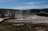 Tourists look at a geothermal feature in the Upper Geyser Basin in Yellowstone National Park, Wyoming on Tuesday, May 23, 2017. (Photo by James Brosher)
