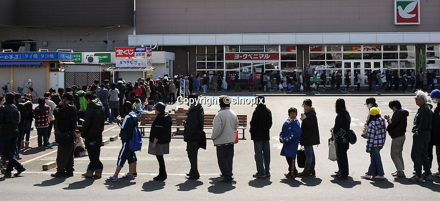 People queue for food in the town of Natori after the Tsunami devastated ahe entire pacifc coastline of Japan after the earthquake and tsunami devastated in the town Natori, near Sendai, Japan. One of the biggest earthquakes ever recorded struck off the coast of Japan on 11 Mar 2011 had killed thousands of people. The death toll was expected to rise dramatically, with tens of thousands reported missing..14 Mar 2011....