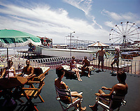 People relaxing on the Kings Inn Sundeck with a view of the ferris wheel and boardwalk rides.