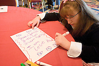 Amy Hughes writes a letter during arts and crafts time at the Share and Care Network's annual retreat held at the Doubletree Guest Suites Hotel in Boston on May 20, 2006. <br /> <br /> The Share and Care Network was created in 1981 by Pat Cahill when her son Scott was diagnosed with Cockayne Syndrome.  A rare form of dwarfism, Cockayne Syndrome is a genetically determined condition whose symptoms include microcephaly, mental retardation, progressive blindness, progressive hearing loss, premature aging, and a shortened lifespan averaging 18 years.  Those afflicted have distinctive facial features, including sunken eyes, pinched faces, and protruding jaws as well as distinctive gregarious, affectionate personalities.<br /> <br /> Because of the rarity of the condition (1/1,000 live births) and its late onset (characteristics usually begin to appear only after one year), many families and physicians are often baffled by children whose health begins to deteriorate after normal development.  It was partly with this in mind that the Share and Care Network was formed, to promote awareness of this disease as well as to provide a support network for those families affected.  In 1998 it began organizing an annual retreat, which has grown from three families in its inaugural year to more than 30 today.  Although the retreat takes place in the United States, families from as far as Japan arrive for this one weekend out of the year to share information and to support one another.