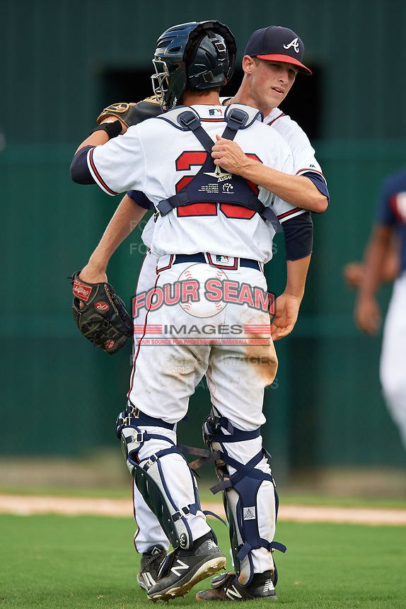 GCL Braves relief pitcher Victor Cavalieri (15) hugs catcher Logan Brown (28) after the final out of the second game of a doubleheader against the GCL Yankees West on July 30, 2018 at Champion Stadium in Kissimmee, Florida.  GCL Braves defeated GCL Yankees West 5-4.  (Mike Janes/Four Seam Images)