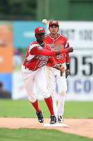 Batavia Muckdogs shortstop Javier Lopez (22) throws to first as third baseman Hiram Martinez (15) backs up the play during the first game of a doubleheader against the Connecticut Tigers on July 20, 2014 at Dwyer Stadium in Batavia, New York.  Connecticut defeated Batavia 5-3.  (Mike Janes/Four Seam Images)