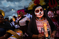 A Mexican girl, dressed as La Catrina, a Mexican pop culture icon representing the Death, takes part in the Day of the Dead parade in Oaxaca, Mexico, 31 October 2019. Day of the Dead (Día de Muertos), a religious holiday combining the death veneration rituals of Pre-Hispanic cultures with the Catholic practice, is widely celebrated throughout all of Mexico. Based on the belief that the souls of the departed may come back to this world on that day, people gather together while either praying or joyfully eating, drinking, and playing music, to remember friends or family members who have died and to support their souls on the spiritual journey.
