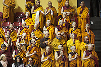 """Switzerland. Basel. St. Jakobshalle. European monks listen to His Holiness the Dalai Lama during a public lecture on Bodhicitta. The topic of the talk is about Nagarjuna's Commentary on Bodhicitta which touches on two aspects of the awakening mind, the twin qualities of wisdom and compassion, which are necessary for anyone who aspires to be a better person and implement changes in their lives. The 14th and current Dalai Lama is Tenzin Gyatso, recognized since 1950. He is the current Dalai Lama, as well as the longest-lived incumbent, well known for his lifelong advocacy for Tibetans inside and outside Tibet. Dalai Lamas are amongst the head monks of the Gelug school, the newest of the schools of Tibetan Buddhism. The Dalai Lama, also called """" Ocean of Wisdom"""" is considered as the incarnation of Chenresi, the Bodhisattva of compassion who is also the protective deity of Tibet. 7.02.2015 © 2015 Didier Ruef"""
