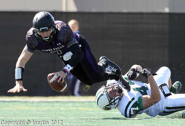 SIOUX FALLS, SD - SEPTEMBER 22:  Taylor Perkins #7 from the University of Sioux Falls is tripped up for a sack by Buckley Wright #47 from Bemidji State in the second quarter of their game Saturday afternoon at Bob Young Field. (Photo by Dave Eggen/Inertia)