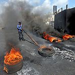 Lebanese protesters burn tyres to block a road in the southern Lebanese city of Sidon (Saida) on March 8, 2021, during a demonstration over a deepening economic crisis that has thrown more than half of the population into poverty. Photo by Haitham Moussawi