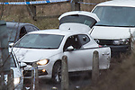 © Joel Goodman - 07973 332324 . 03/01/2017. Huddersfield, UK. A car with smashed passenger side windows , behind a bullet riddled white Audi car at the slip road at Junction 24 of the M62 motorway in Huddersfield . West Yorkshire police have announced a man has died following the discharge of a police firearm , during what they describe as a pre-planned operation , yesterday evening (2nd January 2017) . Photo credit : Joel Goodman