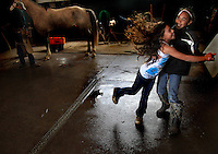 "Nahe Tachera, 9, and sister, Kamehana, 11, dance in the Kahua Ranch barn while their father, Wayne, shoes a horse in North Kohala, Hawaii.  The girls' great-grandfather, grandfather and father are or were all cowboys and they live in ""cowboy housing"" on the ranch because their father is employed as one of the ranch's cowboys.  The girls learned to ride horses as toddlers and have grown up with the ranch as their playground. ""My dad's work is great.  While he works, we can play around the ranch and he doesn't have to worry about us"", says Nahe."