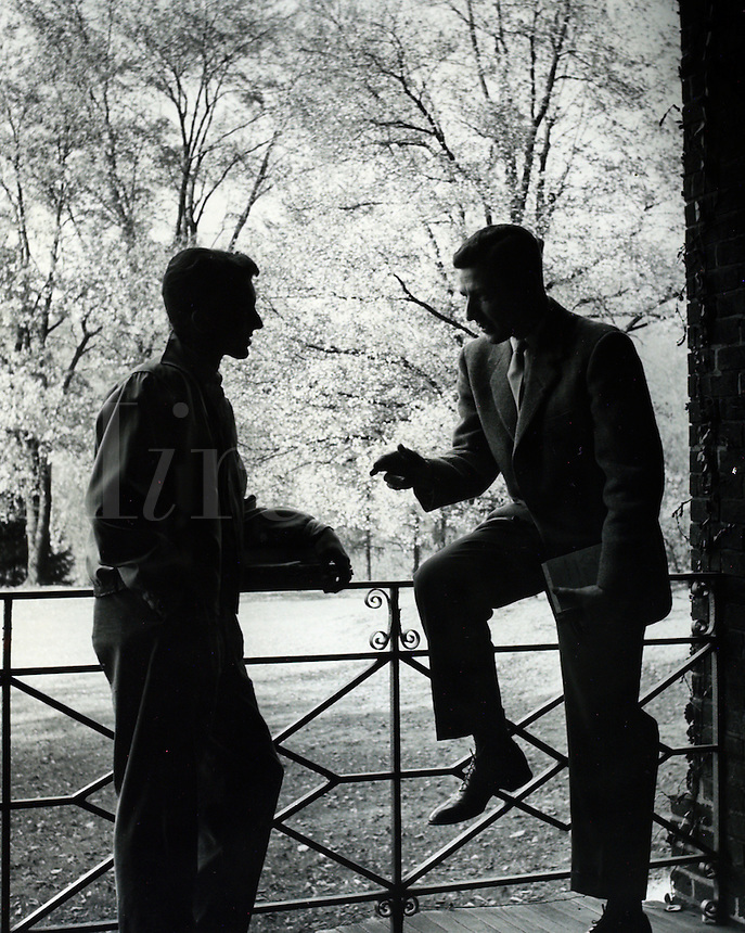 Two young men conversing in outdoor scene. 1950's/