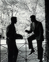 Two young men conversing in outdoor scene. 1950's/