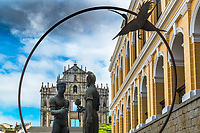 Friendship Statue with the beautiful façade of the Saint Paul cathedral ruins under a cloudy, blue morning sky, Macao China