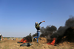 a palestine protester throw stones towards israeli soldiers during clashes near the border fence between israel and east of gaza of bureij camp on october 15,2015. Photo by Osama Baba