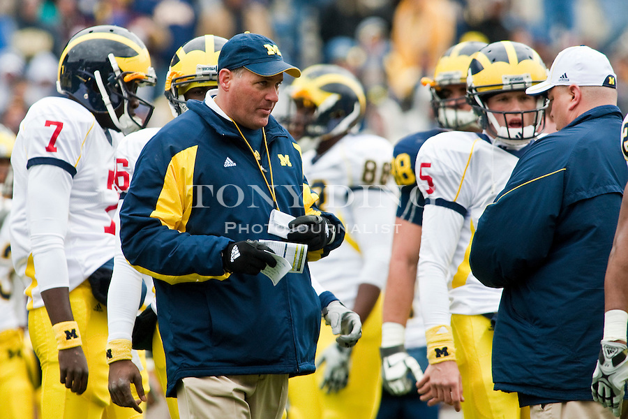 Michigan's quarterbacks gather around head coach Rich Rodriguez, center, as he talks with quarterbacks coach Rod Smith, right, before the Wolverines' spring football game, Saturday, April 17, 2010, in Ann Arbor, Mich. (AP Photo/Tony Ding)