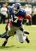 New York Giants wide receiver Plaxico Burress (17) is tackled by Philadelphia Eagles defender Joselio Hanson and fumbles the ball into the end zone which was recovered for a touch down by Giants teammate Tim Carter for a touchdown in the fourth quarter in a NFL game in Philadelphia, Spetember 17, 2006. The Giants beat the eagles 30-24. REUTERS/Bradley C Bower (UNITED STATES)
