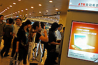People queue at ATM machines in Guangzhou, Guangdong Province, China. Despite the general economic down-turn China's domestic demand is helping China to maintain positive economic growth..