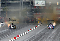 Mar 29, 2014; Las Vegas, NV, USA; NHRA top fuel dragster driver Scott Palmer loses some of the bodywork from his car racing alongside Mike Strasburg during qualifying for the Summitracing.com Nationals at The Strip at Las Vegas Motor Speedway. Mandatory Credit: Mark J. Rebilas-