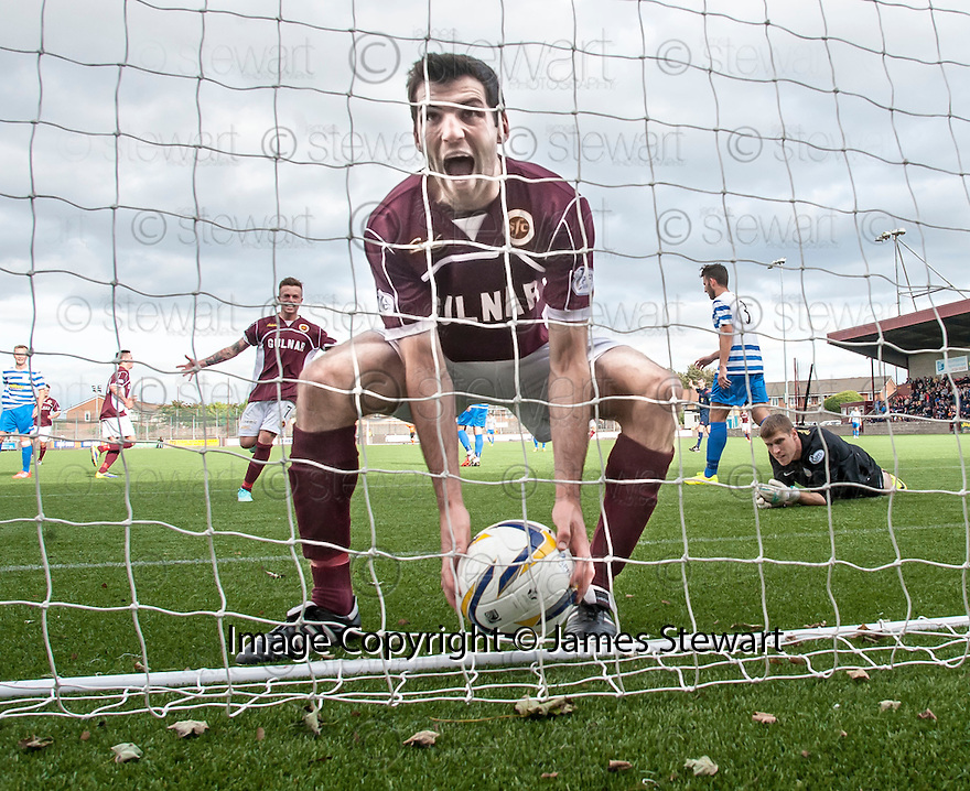 Stenny's Martin Grehan picks the ball out of the back of the net after he scores their first goal.