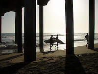 Surfers walk under the Huntington Beach Pier looking for waves.