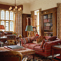 The stuccoed library has carved wooden bookshelves and is decorated with an eclectic mix of fabric