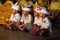 Bali, Indonesia.  Young Boys Watching Dancer Re-enacting Scenes from Balinese Hindu Mythology, part of a ceremony in hope of a bountiful rice harvest.  Pura Dalem Temple, Dlod Blungbang Village.