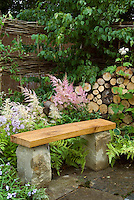 Stone bench on patio in backyard garden, with flowers, ferns, privacy